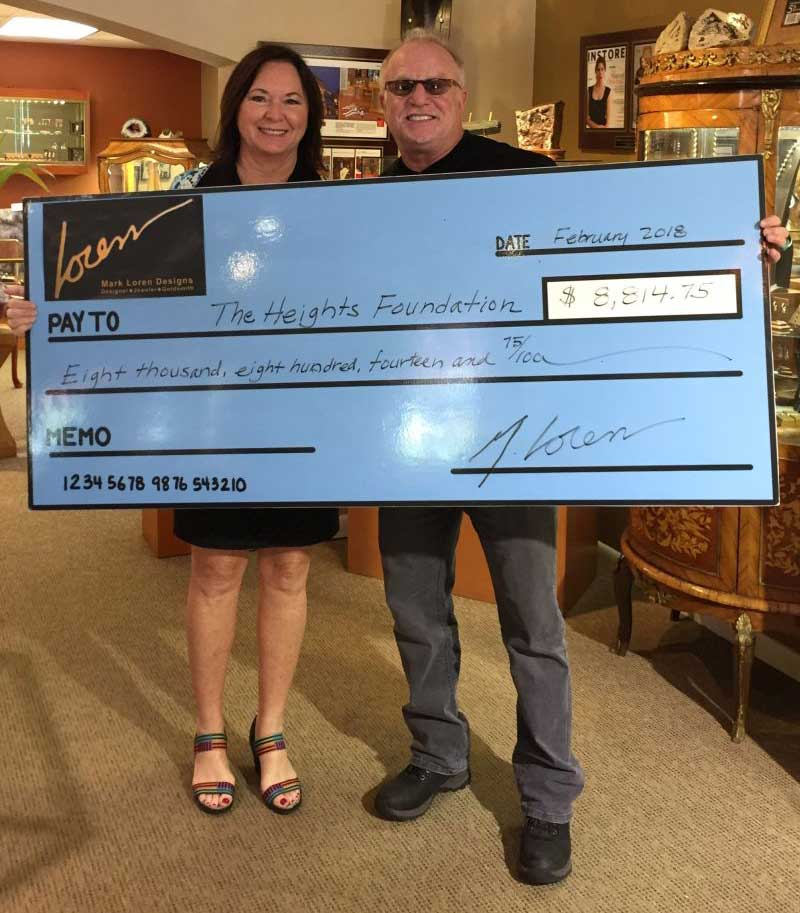 Mark Loren and a female holding a check to The Heights Foundation in the amount of $8,814.75