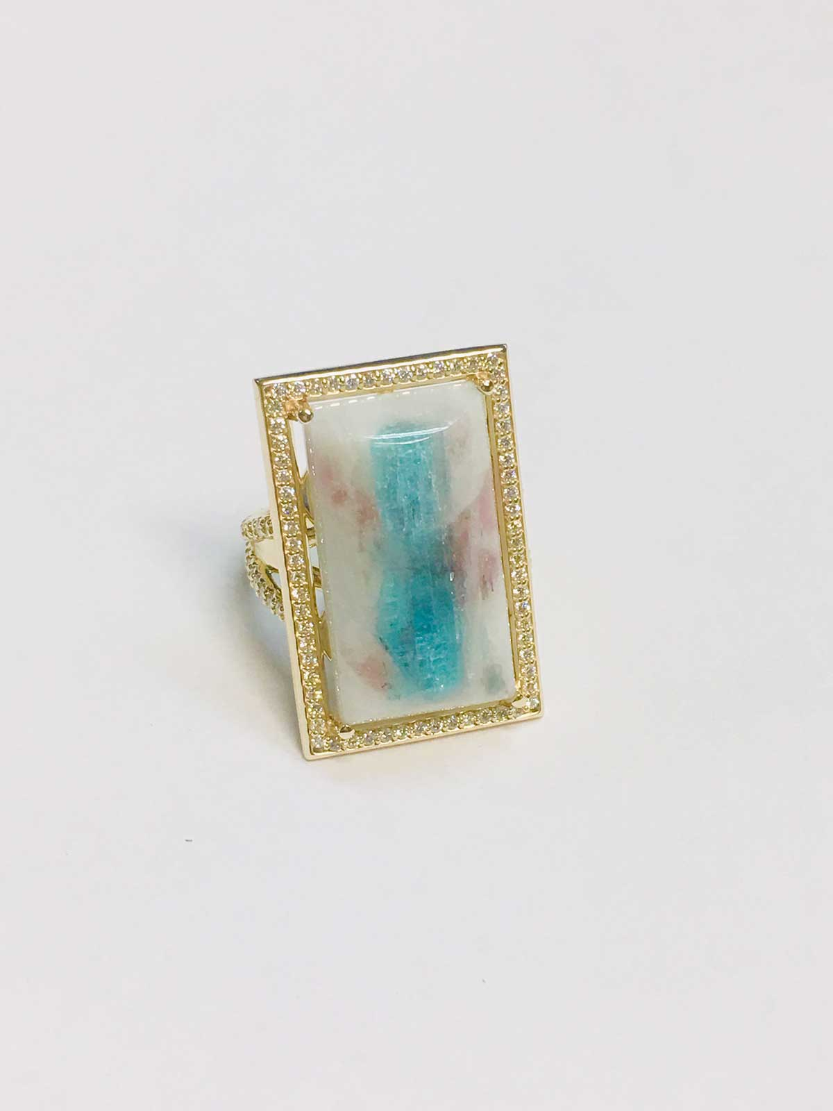 A dramatic and feminine, 14k yellow gold ring framing a rare, Cabachon-cut, Paraiba Blue Tourmaline crystal with pink Tourmaline crystals in white Quartz. Pave-set Diamonds form the border