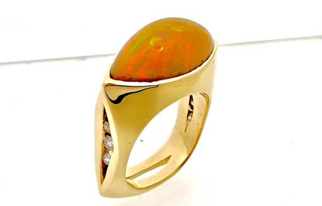 18k yellow gold ladies ring showcasing a spectacular, FireOpal accented with Channel-set Diamonds