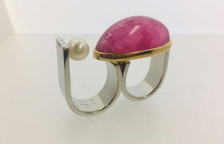 Powerfully dramatic two-finger ring in Platinum and 18k yellow gold showcasing a rare, cats-eye pink Tourmaline accented with an Akoya Pearl and a Diamond baguette