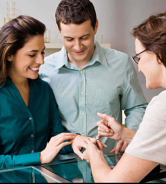 Woman appraising jewelry for couple
