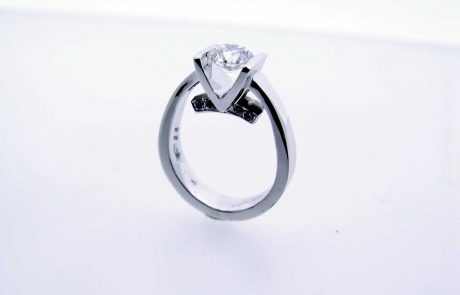 One of a kind engagement ring in white gold with a tension-set Brilliant Diamond and accent Diamonds underneath
