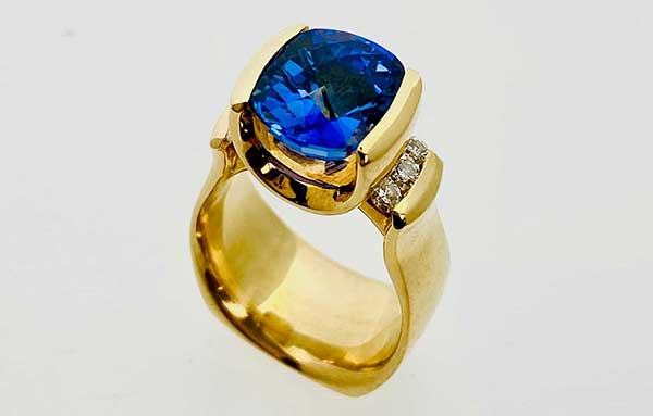 Luscious, deep blue, tension-set Tanzanite accented with channel-set Diamonds in 18k yellow gold