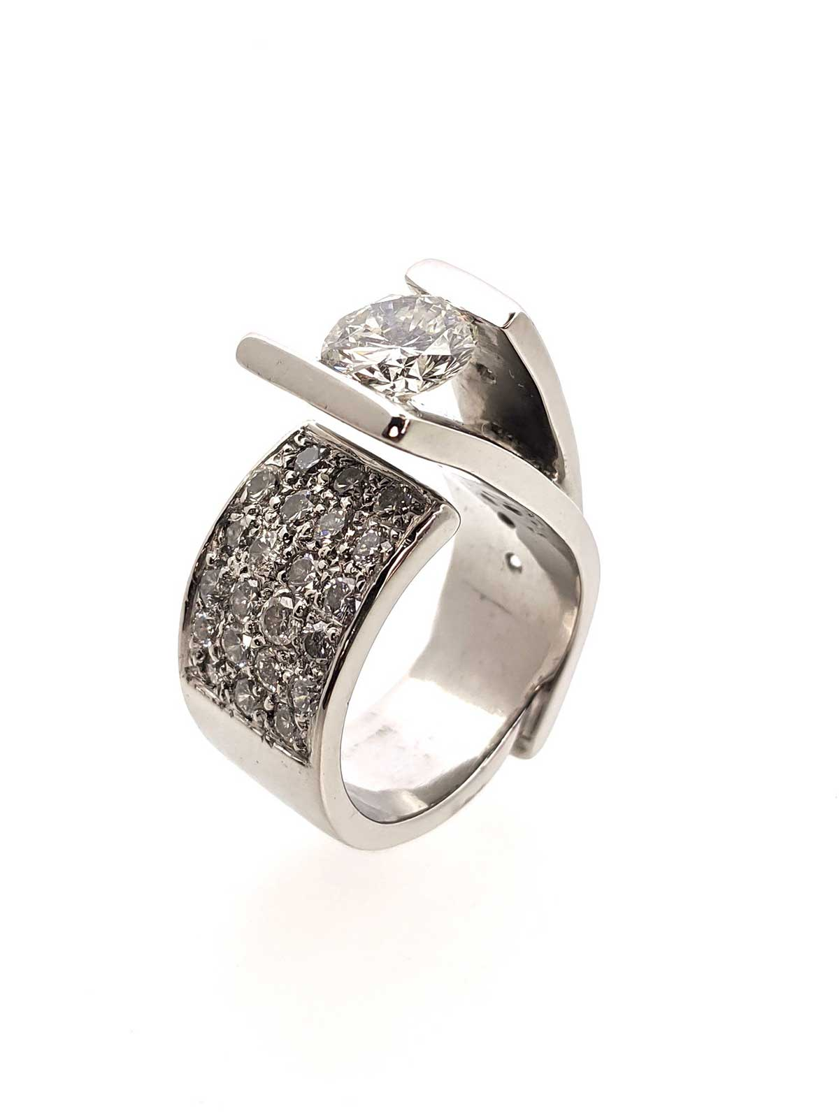 Tension-set diamond in a white gold asymmetrical split ring with pave set diamonds on the opposite side