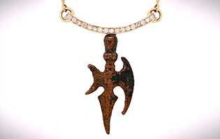 Ancient bronze Saracen battle axe amulet suspended from tension-set diamonds in 14k yellow gold