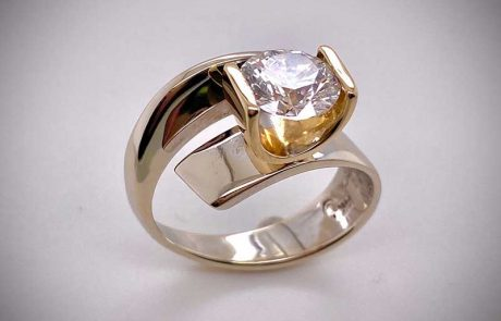 Simple and dramatic tension-set split ring in white gold featuring engagement diamond in yellow gold mirror-mount