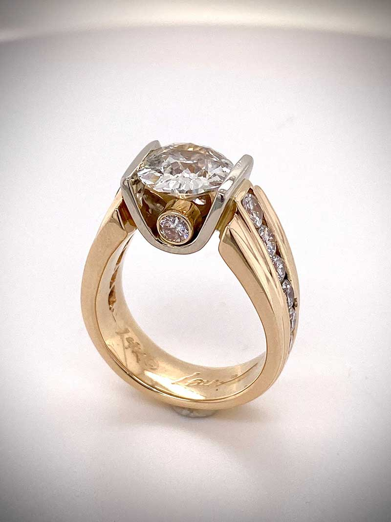 Tension-set diamond ring mounted in 14k white gold diamonds as accents in yellow gold