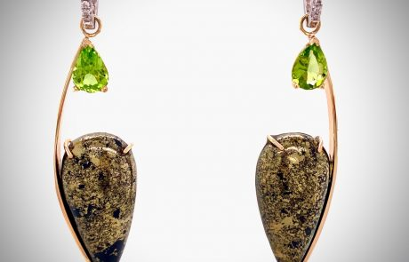One-of-a-kind ear pendants forged in 14k yellow gold and showcasing a pair of teardrop Apache Gold stones and accented with pearshape-cut Peridot gems
