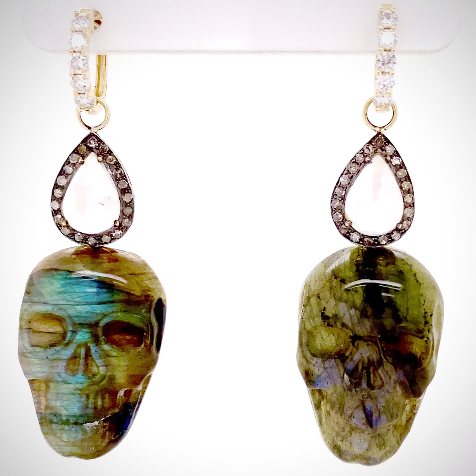 One-of-a-kind pair of carved Spectralite skulls accented with Blue flash Moonstone pear shapes surrounded by Diamonds