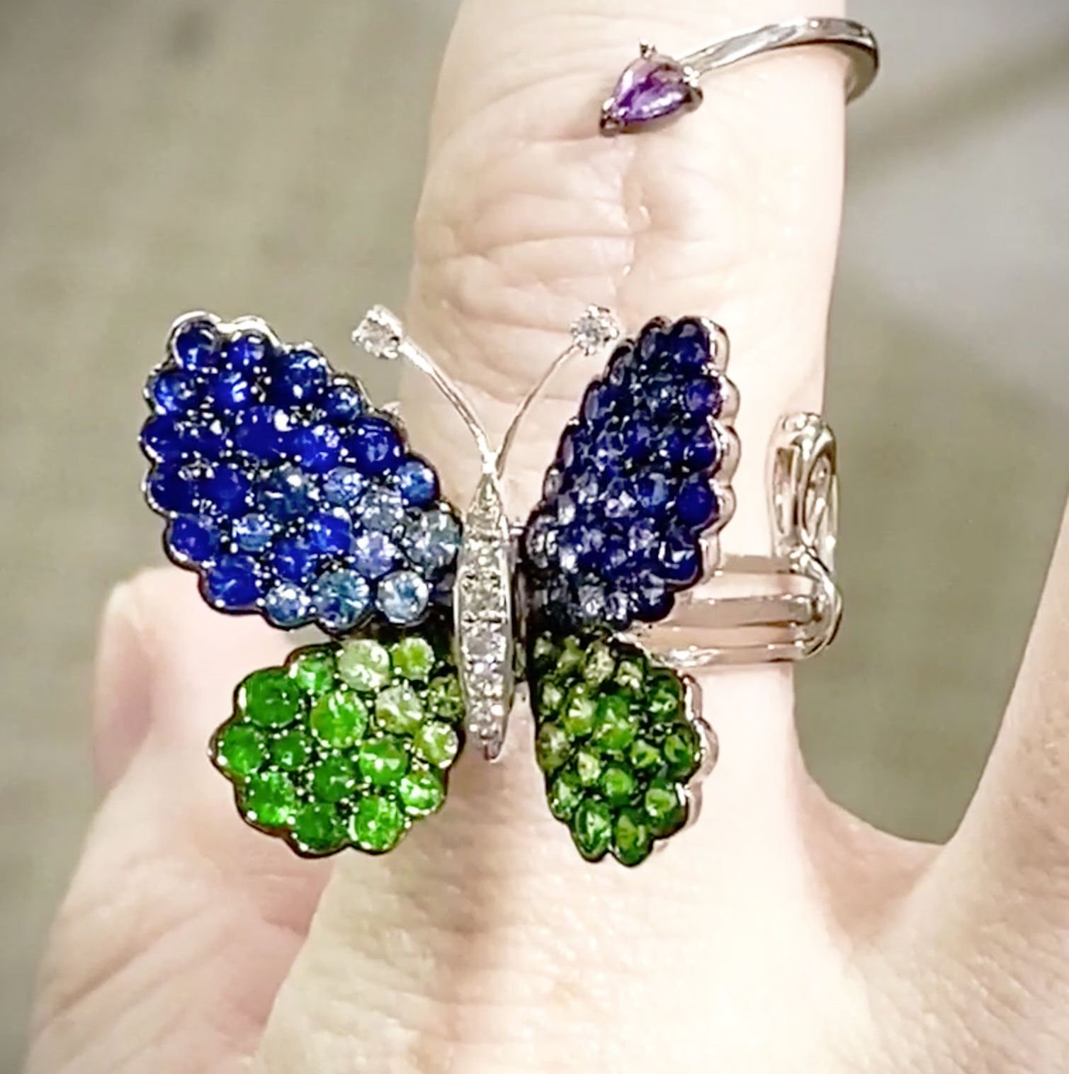 Articulated butterfly ring in 18k white gold set with Tsavorite Garnets, Blue Sapphires and Diamonds… as fingers bend, the wings close and open!