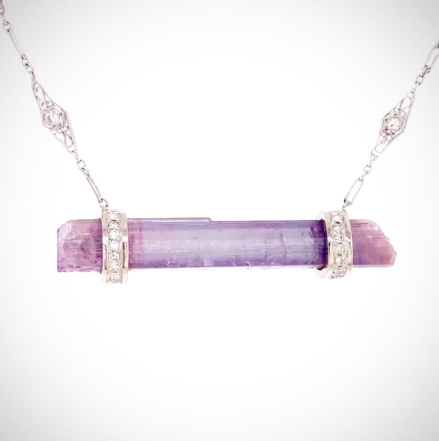 Incredibly rare Mozambique lavender Tourmaline crystal framed with 14K white gold Diamond collars and suspended from a vintage platinum Diamond chain