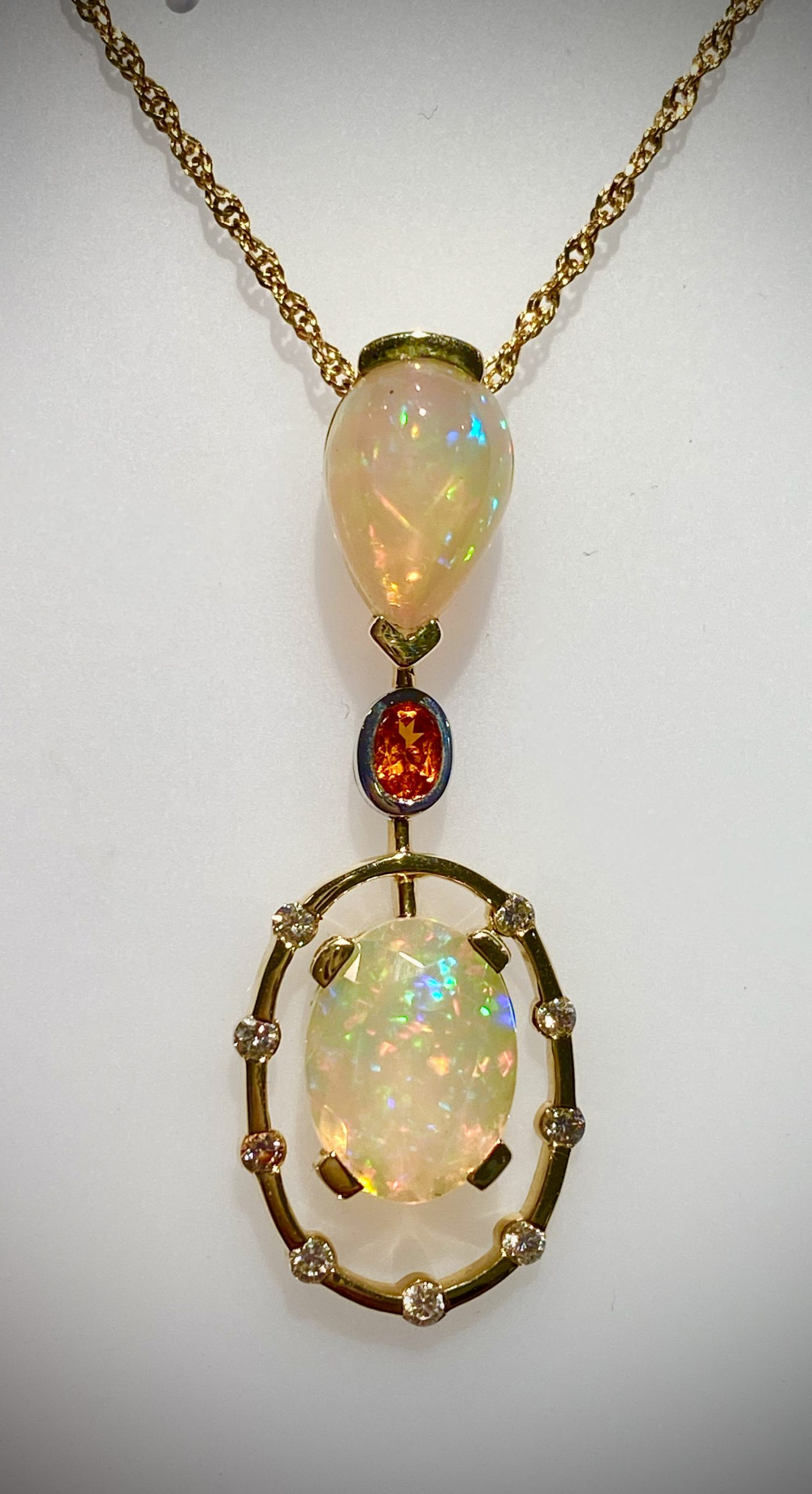 A beautifully feminine 14K pendant framing two Faceted Ethiopian Opals accented with Diamonds and a petite Orange Sapphire