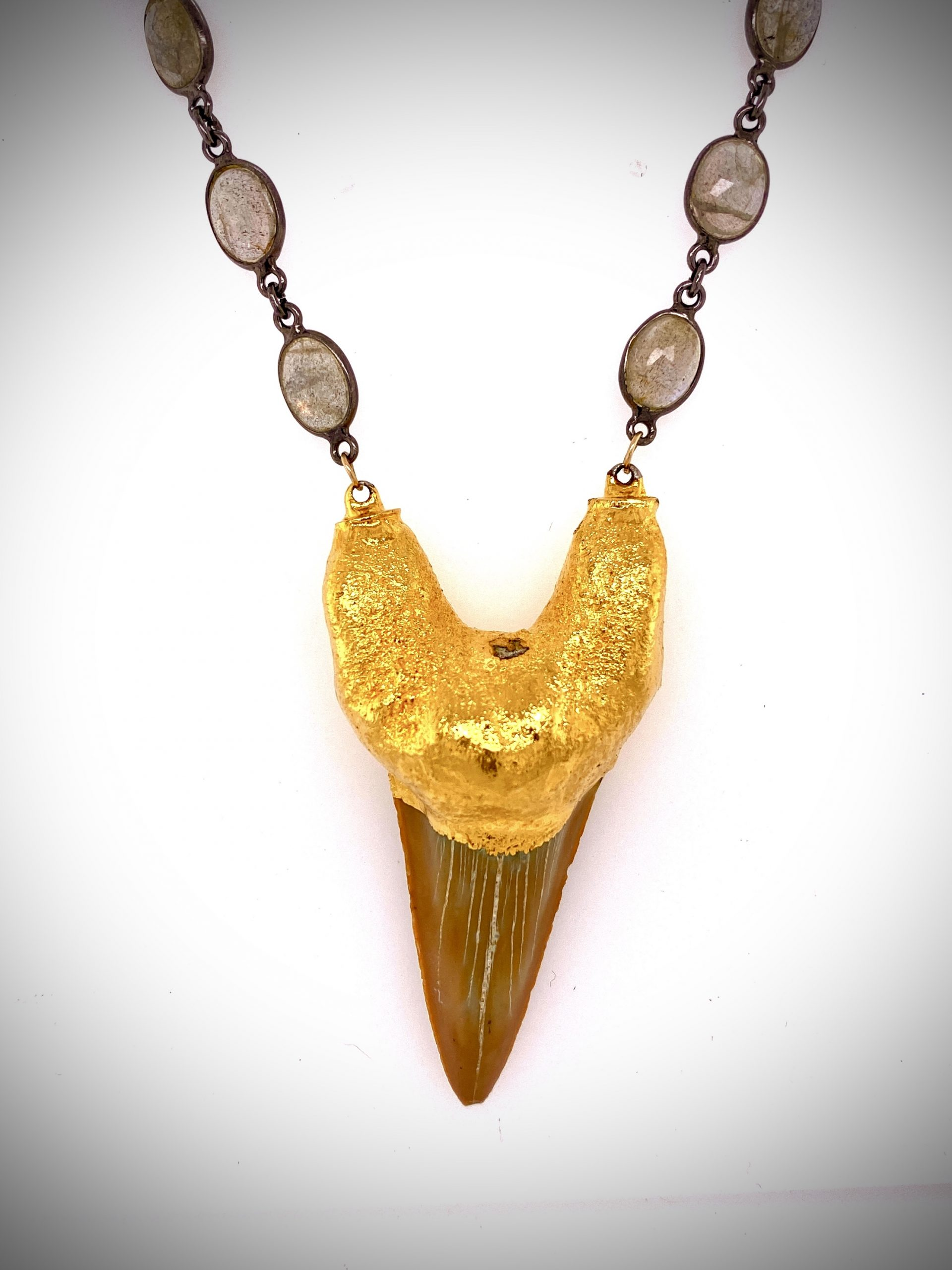 A dramatically simple necklace using a large fossilized Shark's tooth gold formed with 14K yellow gold and suspended from a handmade sterling chain set with faceted Spectralite beads