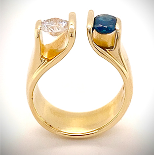 A vintage custom designed Mark Loren split ring tension sets our clients round brilliant Diamond and an oval Blue Sapphire