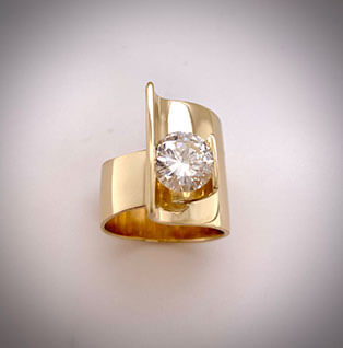 Our classic asymmetrical and dramatic gold ring tension-setting a 3ct round brilliant diamond.