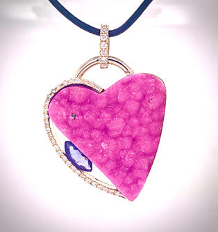 An incredibly bright pink Cobalto Calcite heart-shape is accented with pave-set diamonds and a tension-set lavender sapphire marquise in this 14K gold pendant.