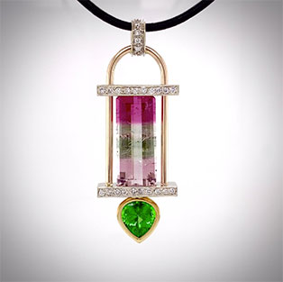 Pendant crafted in tri-color gold with a tension-set spectacular multi-color, rectangular tourmaline and offset with a bezel-set pear shape tsavorite of exceptional color accented with pave-set diamonds.