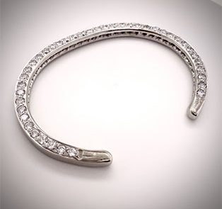 Our custom hand-forged 14K white gold cuff bracelet, pave-set on one side with 8.50cts of fine diamonds.