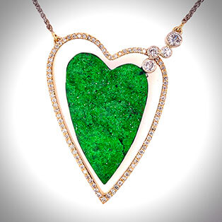 This one of a kind 14K yellow gold necklace floats, framing a spectacular Russian, heart-shaped uvarovite accented with bezel-set diamonds.