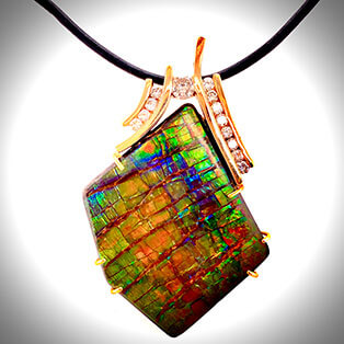 An amazing 14K yellow gold pendant suspending a fossil opal, accented with channel-set diamonds.