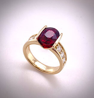 A custom designed 18K yellow gold ring that tension-sets a spectacular Mozambique ruby and is accented with channel-set diamonds down the sides.