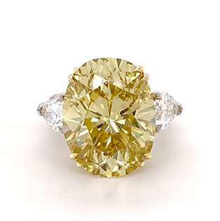 A monumental 19ct fancy yellow oval diamond accented with pear shape white diamonds in 18K gold and platinum.