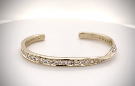 Hand-forged with a twist, this 14K yellow gold cuff bracelet is completely pave-set with diamonds.