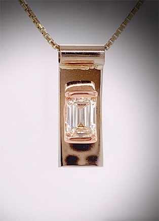 Custom-designed pendant for our client using their 2ct emerald-cut diamond, tension-set in rose and white gold.