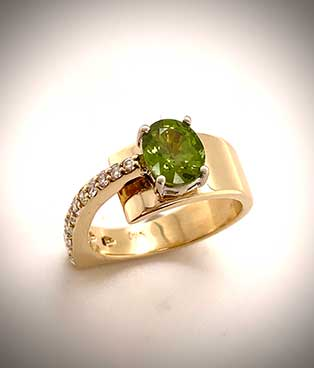 Custom-designed 14K yellow gold ring displays an oval-cut, green zircon and is accented with diamonds.