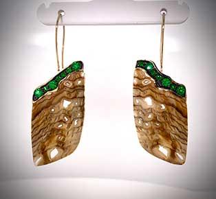Custom-designed earrings feature fossilized Sequoia wood and pavé-set tsavorite green garnets.