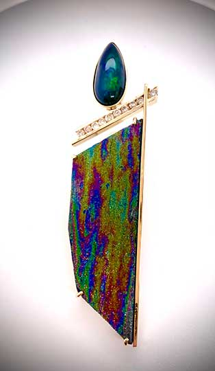 Stunning pendant in 14K yellow gold showcases a rare, rainbow-hued speculated hematite accented with a smoked Ethiopian opal and channel-set diamonds.