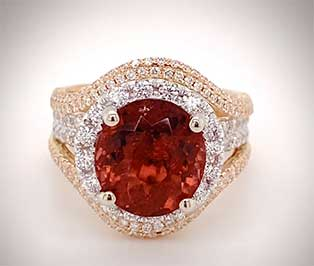 Luscious 18K gold ring displays a large raspberry tourmaline framed with diamonds