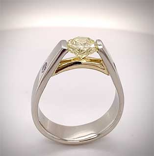 This custom-designed ring is tension-set with our client's diamond solitaire