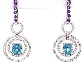 These colorful, removable ear pendantsareset with cushion-cut, Cambodianbluezircons surrounded bydiamondsthat arehanging fromhuggiesset withpurplesapphires in 14Kwhite gold.