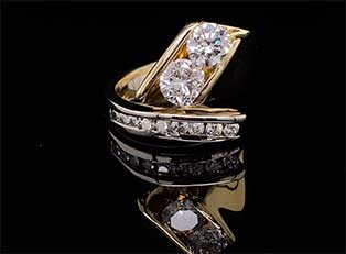 Dramatic, one-of-a-kind, two-tone 14K ring with tension-set diamonds features a curving channel of smaller diamonds.